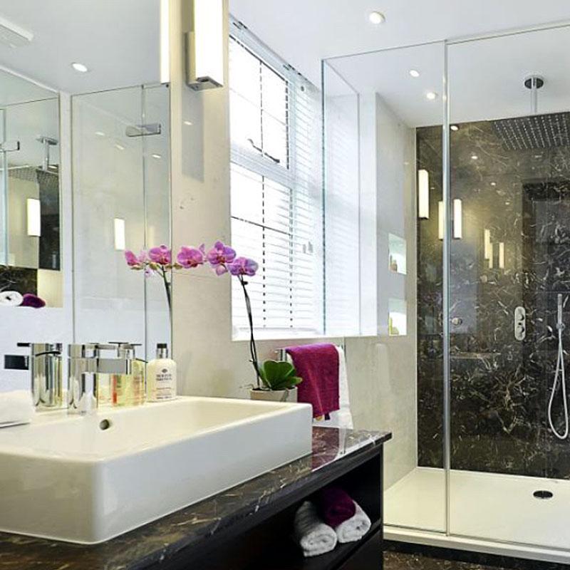 A large frameless glass shower enclosure