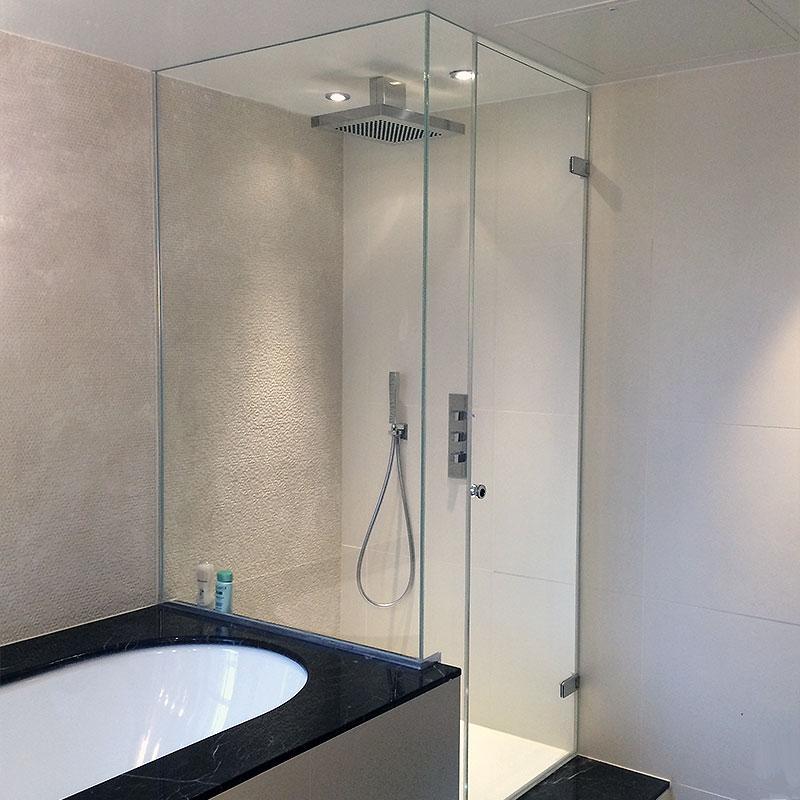 Frameless glass shower by bath tub