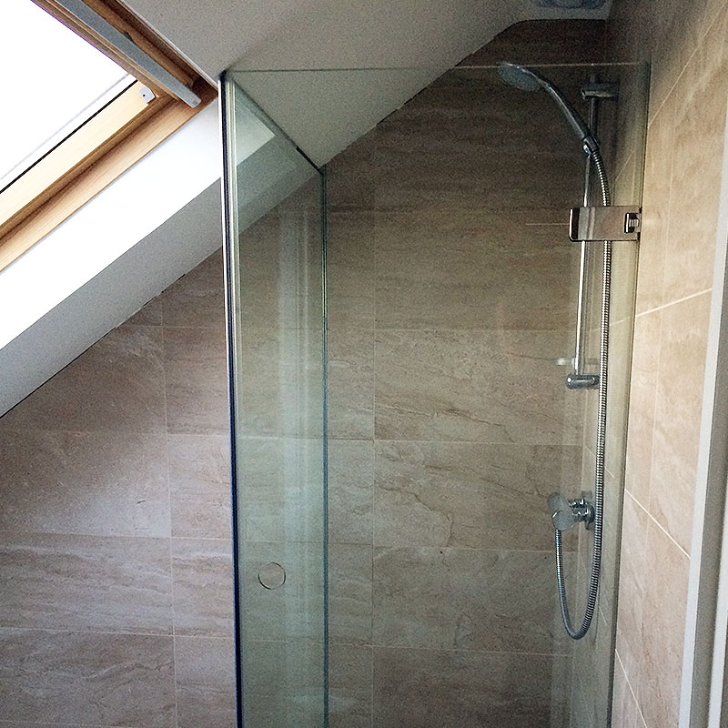 Frameless glass shower in West London which fits in with alignment of sloping roof