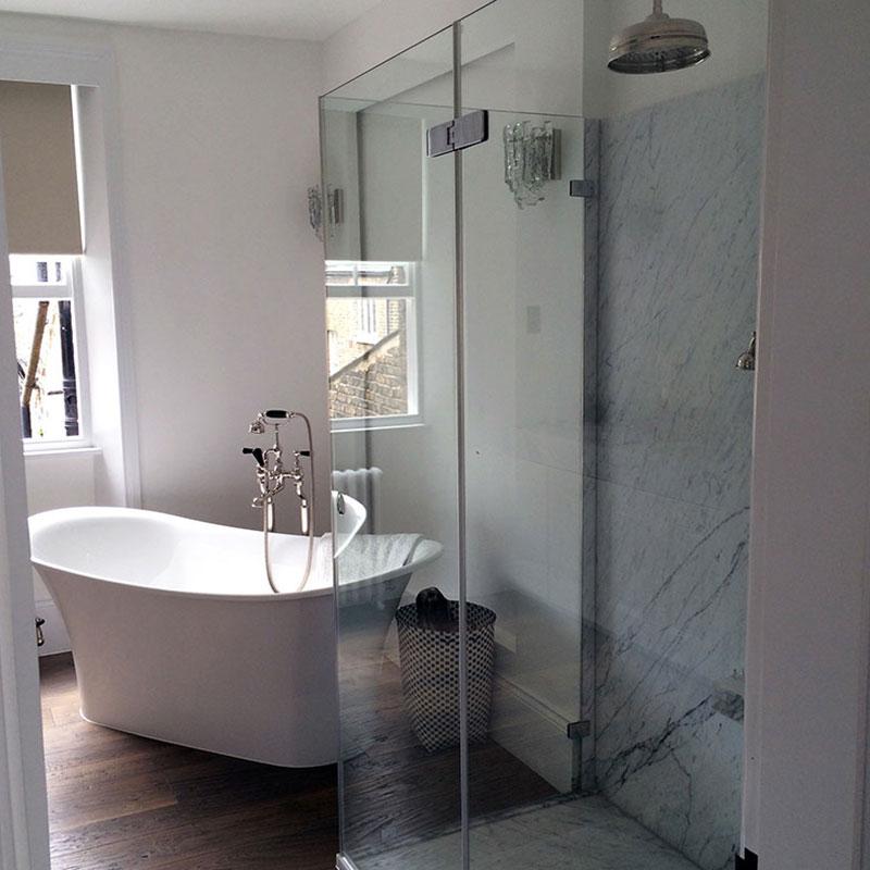 Frameless Glass Shower beside a bath