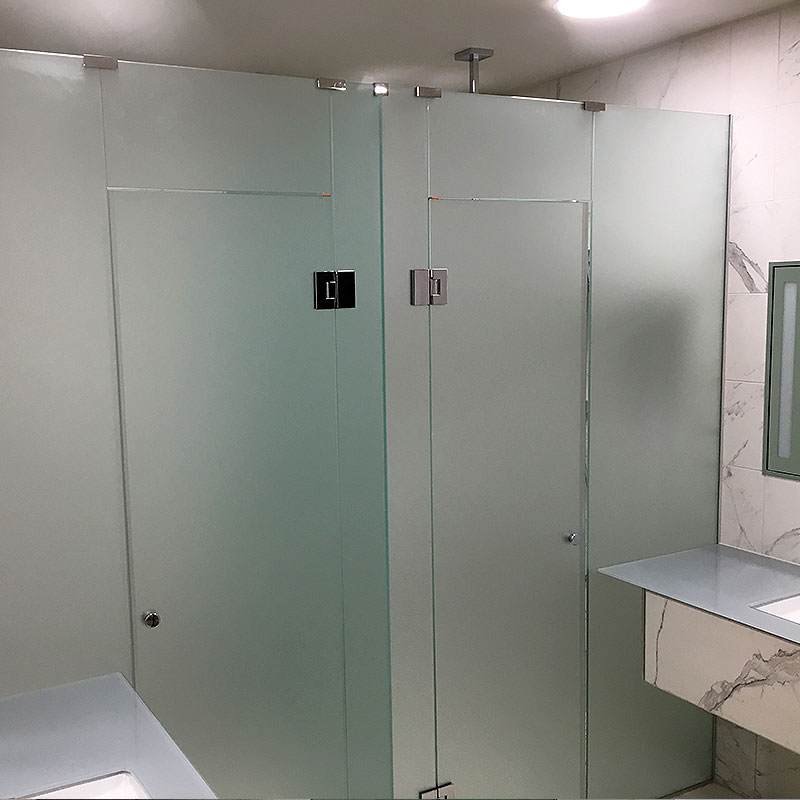 Frosted glass bathroom cubicles with doors closed