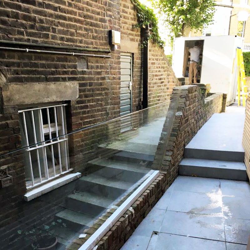 An external glass balustrade providing light and space in place of a brick wall