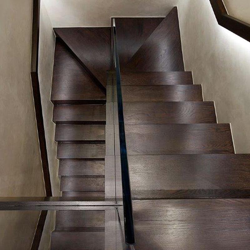 Glass balustrade on dark wood interior staircase