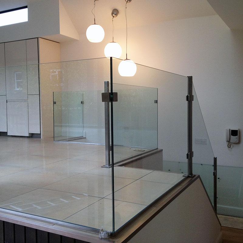Glass balustrades surrounding kitchen mezzanine