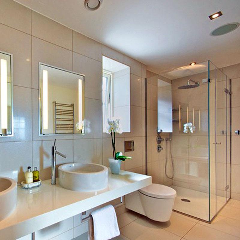 Frameless glass shower in corner of bathroom