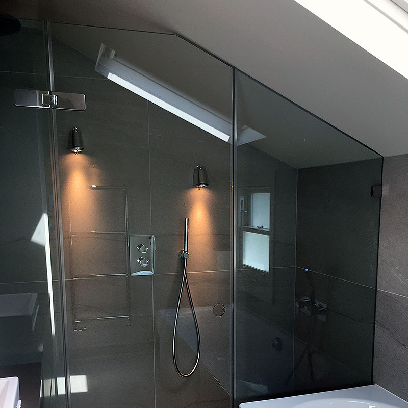 A glass shower which matches the curve of the roof