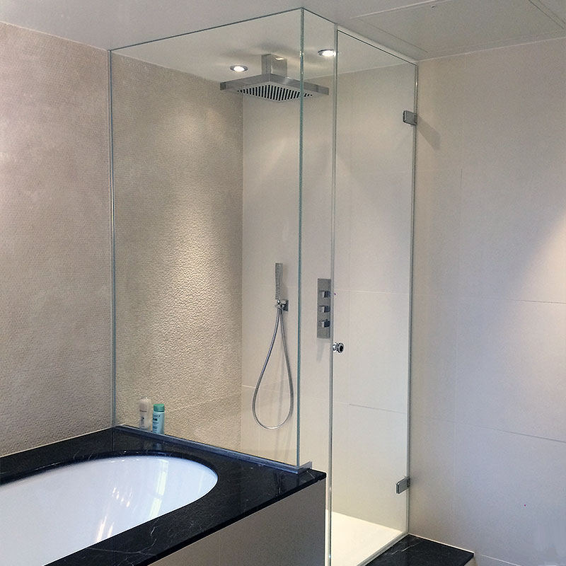 Frameless glass shower by bath tub