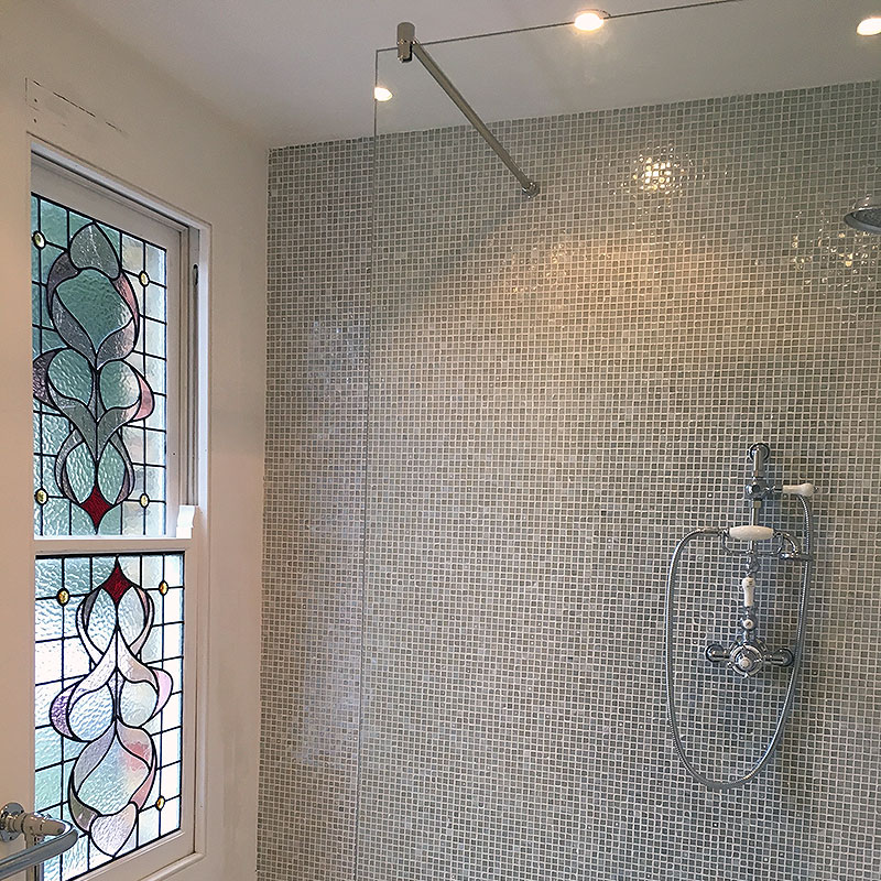 Frameless glass shower suspended from ceiling rail