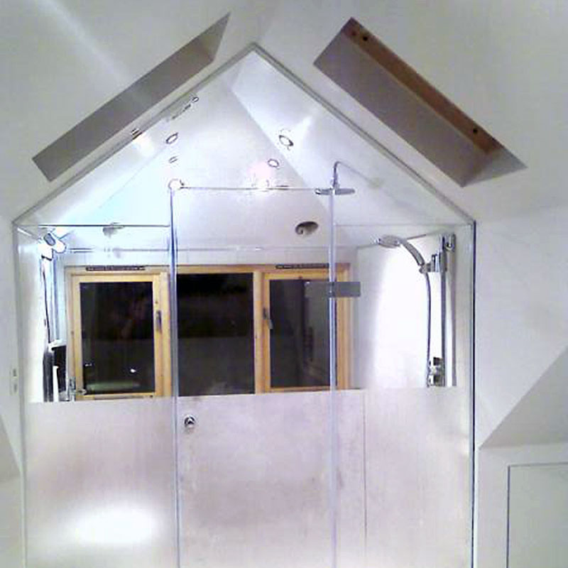 Bespoke glass shower doors cut to match slope of interior roof